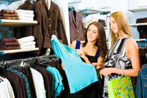 Photo of two girls in the clothing store holding a blue dress and looking at it with smiles on the background of different clothes